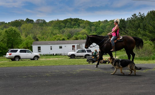 Karolyn Chambers rides her horse past the Cummins' house on Charles Brown Road Monday, April 29, 2019, in Westmoreland where six people were found dead the previous Saturday.
