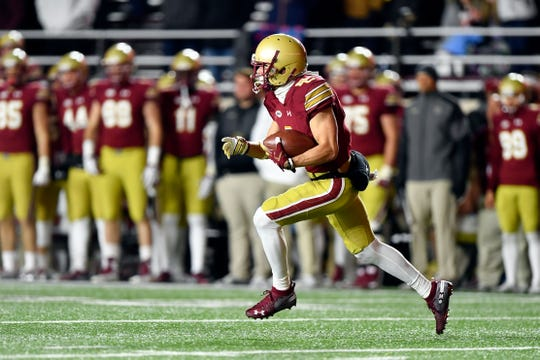 Naples High graduate Michael Walker returns the ball during the second half of Boston College's game with Clemson in November. Earlier, Walker returned a punt 74 yards for a touchdown in the Eagles' 27-7 loss. Walker's brother John and Katie Kramer - daughter of Naples coach Bill - got engaged earlier that day and were on hand to see Walker's big performance.
