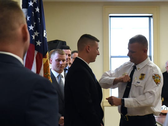 Newark City Police Chief Barry Connell (right) gives an extra punch to the badge of new police officer Robert Brown. Brown asked Connell to pin his badge on him because both men had served in the Coast Guard. The police department swore in seven new officers during a ceremony on Monday, April 29, 2019.