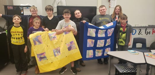 Lakewood Middle School teacher Jessica Bowden (upper right) and her students show off the quilts they made and donated to the Inn at Chapel Grove nursing home.