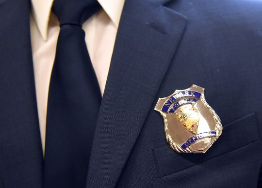 A Newark Police badge on the jacket of newly sworn in officer Jacob O'Neal. New badges will be given to the officers, with their badge number, after they complete seven month of training at the Police Academy in Columbus.