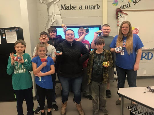 Lakewood Middle School teacher Jessica Bowden (upper right) and her students display the rocks they painted with messages of kindness, and placed throughout Hebron and Buckeye Lake.