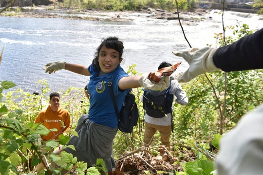 Seven Paterson schools participated in the seventh annual Earth Day Clean-Up of the Great Falls National Historic Park on Monday, April 29, 2019. Paula Rodriguez, 19, from the ACT Academy at John F. Kennedy High School passes trash to a classmate.