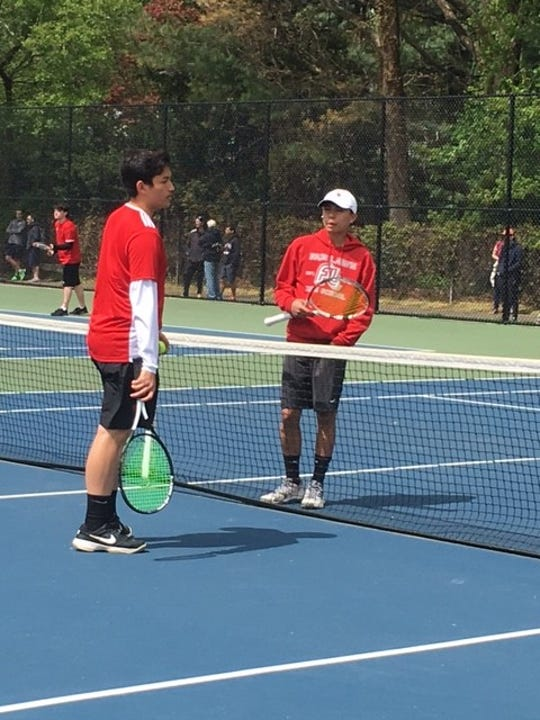 Bergenfield senior John Sangalang, left, and Fair Lawn sophomore Jasper Tumbokon talk at mid-court prior to their matchup at third singles in Saturday's inaugural boys' tennis Spring Invitational Tournament at Northern Valley-Old Tappan High School.
