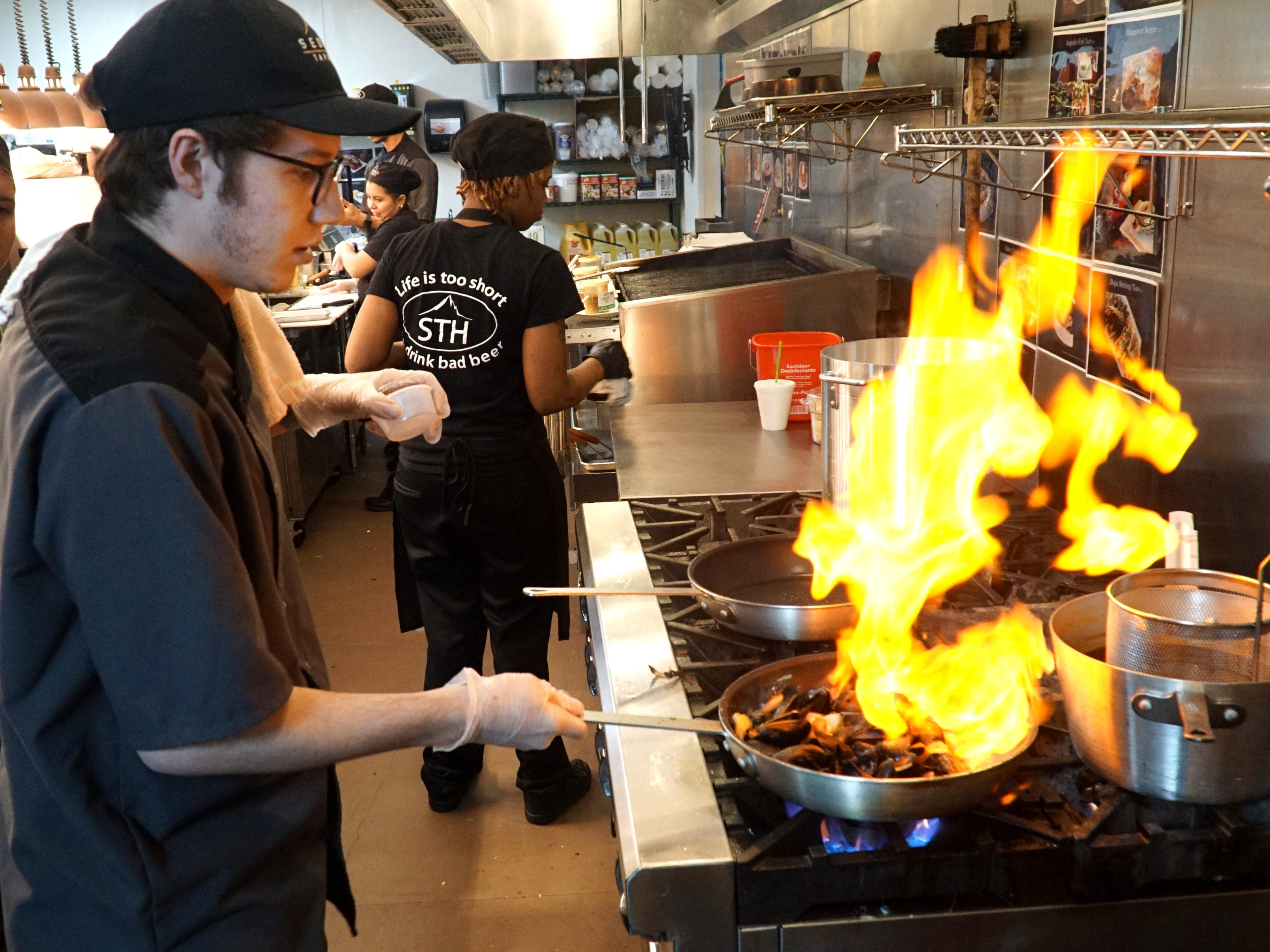 A dash of liqueur goes up in flames as trainer of Sedona Taphouse chefs Tyler Barbaro whips up a sautee pan of Prince Edward Island mussels on April 29 - as the Twelve Oaks Mall restaurant gets ready for its opening night.
