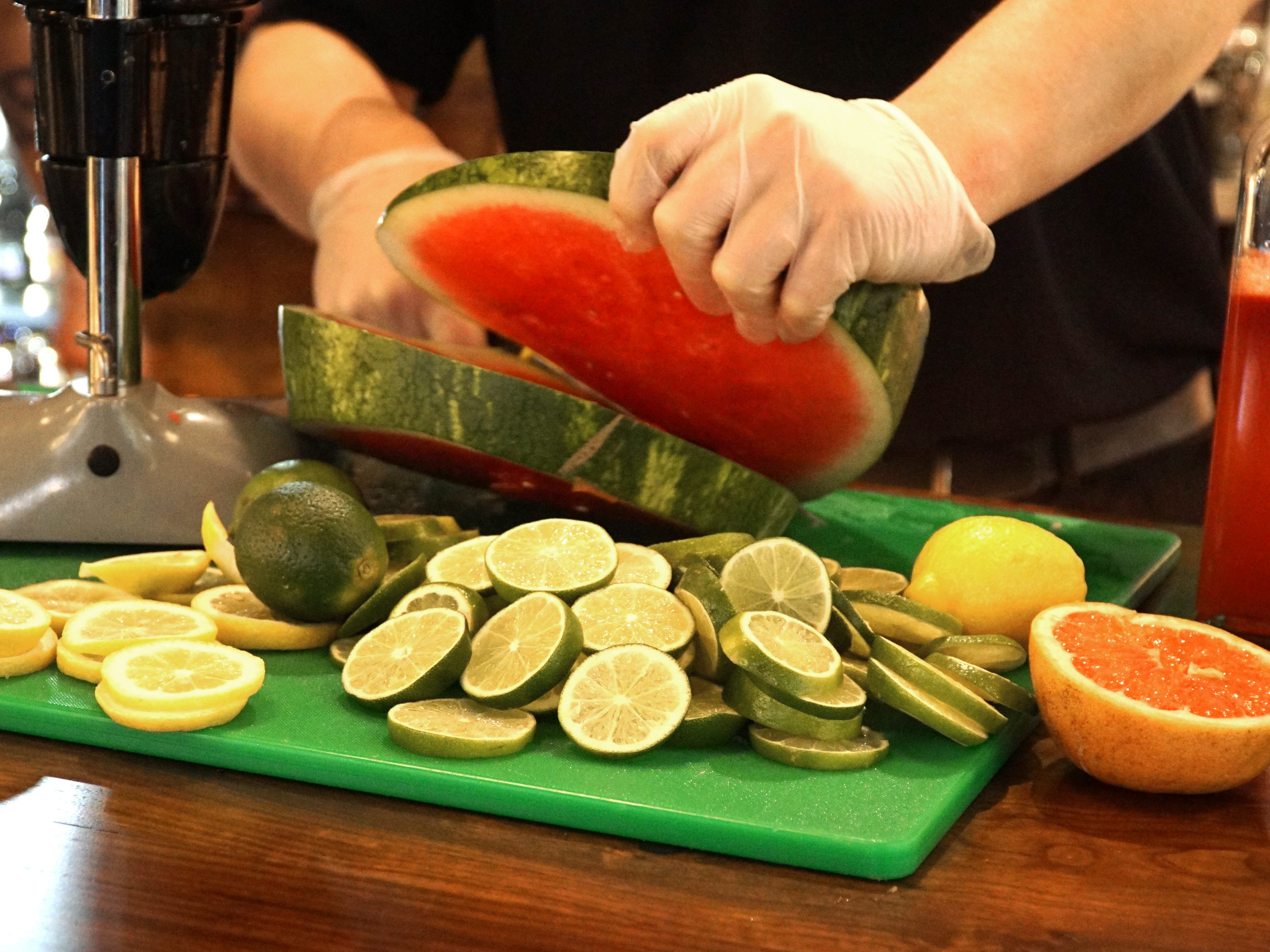 A Sedona Taphouse bartender cuts up fruits for mixed drinks.