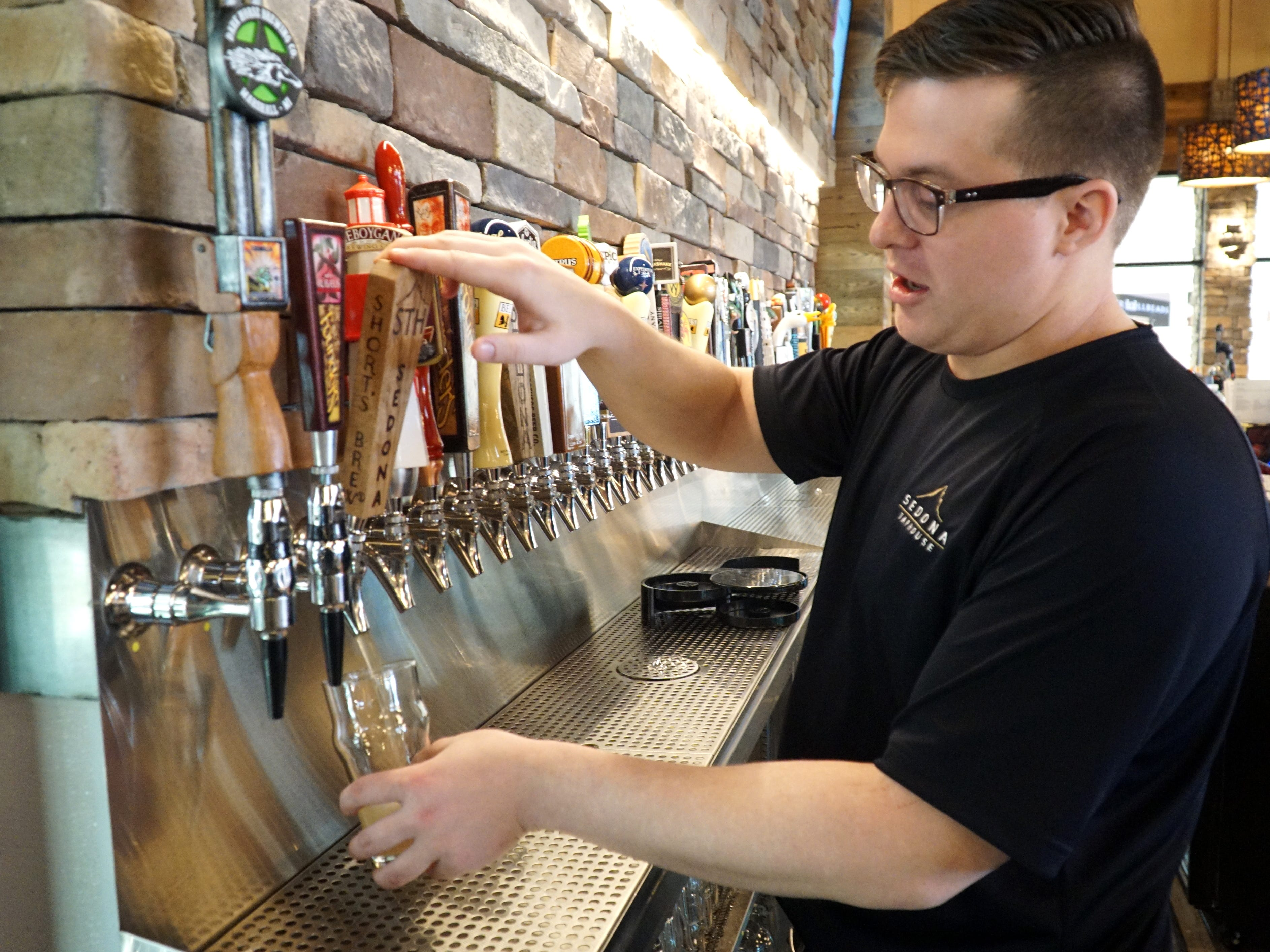 Sedona Taphouse bartender Jake Ockert draws a beer from one of the restaurant's 50 brews on tap on April 29. The Novi restaurant also has 200 varities of beer in bottles and cans.