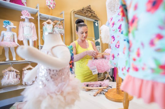 Owner Kelly Taylor gets merchandise ready to hang at Properly Posh Baby in downtown Pensacola on Monday.