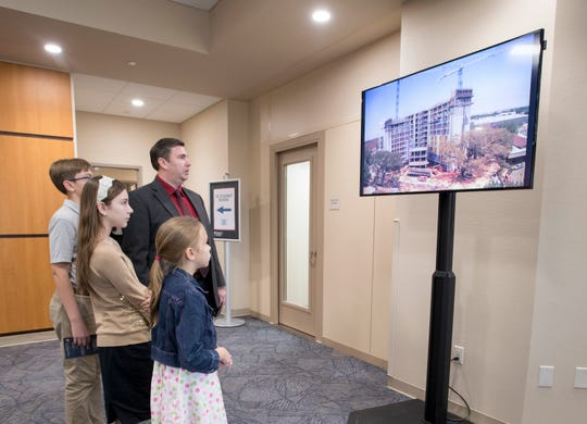 The Sleeth family watches a timelapse video of the construction of the new Rice Tower residence hall during an open house Monday at Pensacola Christian College.