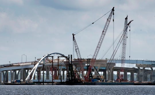 An arch for the new bridge under construction over Pensacola Bay rests next to the replacement structure on Monday, April, 29, 2019. The arch is one of signature design features of the new bridge.