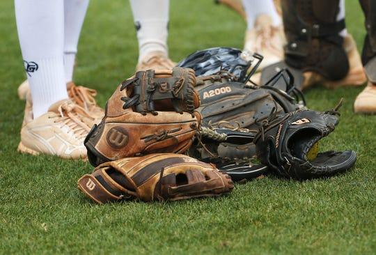 Softball gloves at the Hamilton High softball field in Chandler, Ariz.