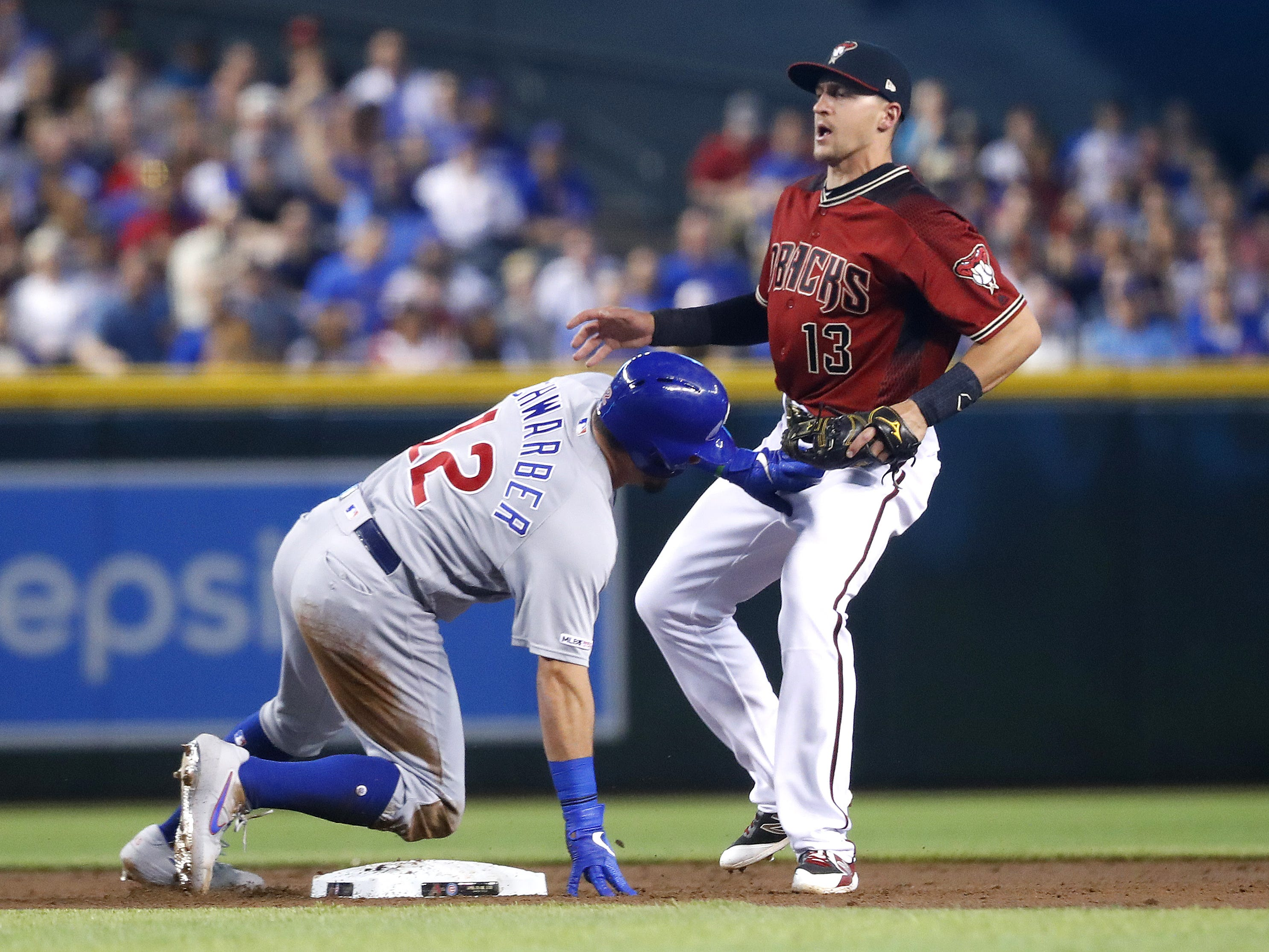 Diamondbacks' Nick Ahmed backs off Cubs' Kyle Schwarber (12) after recording an out at second base during the second inning at Chase Field in Phoenix, Ariz. on April 28, 2019.