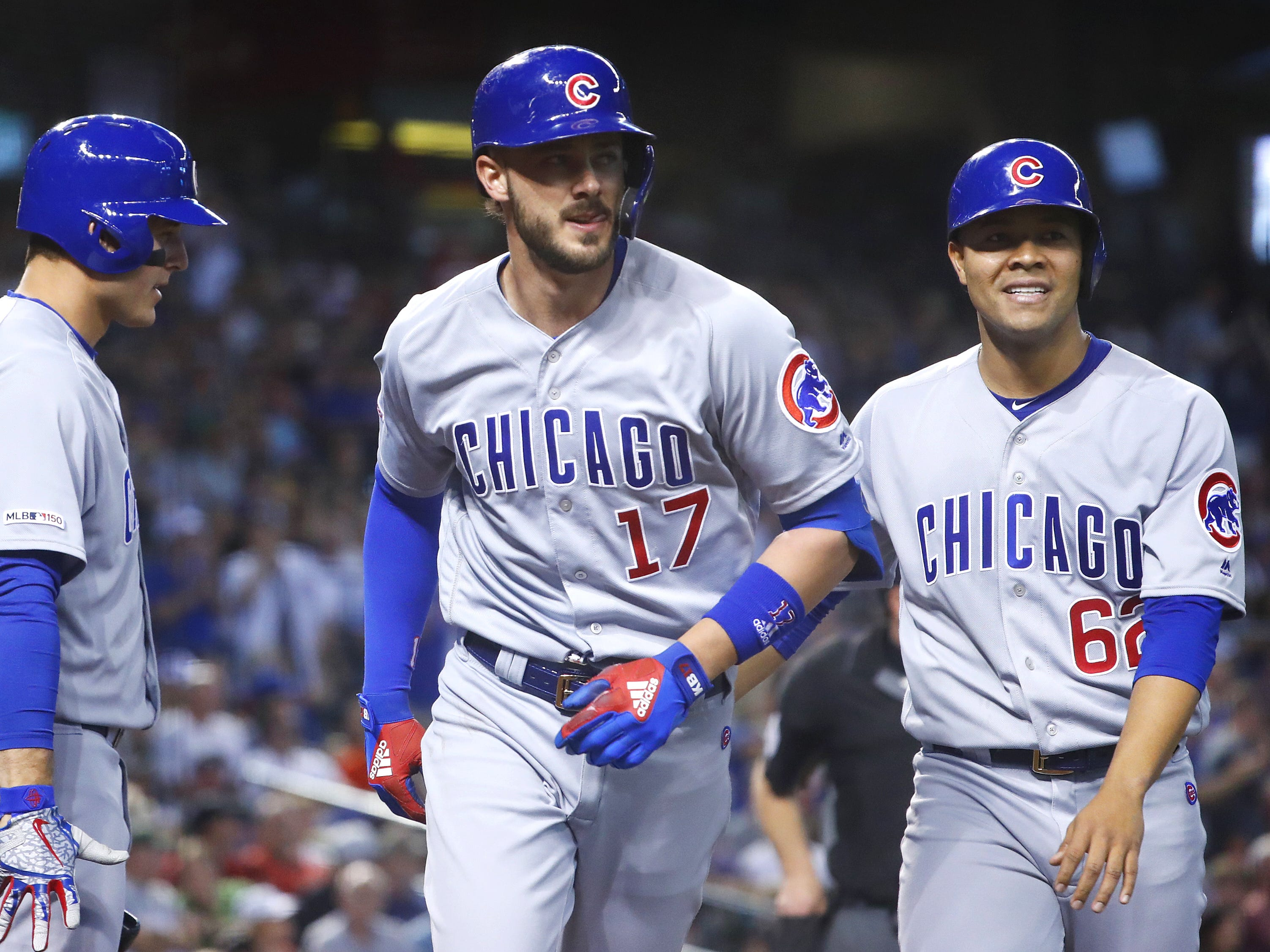 Cubs' Kris Bryant (17) celebrates with pitcher Jose Quintana (62) and Anthony Rizzo (44) after hitting a two-run homerun against the Diamondbacks during the third inning at Chase Field in Phoenix, Ariz. on April 28, 2019.