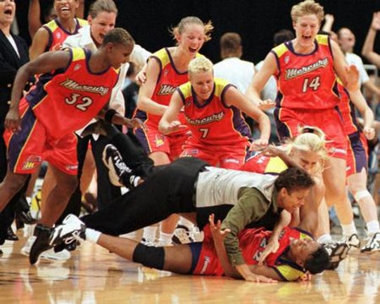 Jennifer Gillom is mobbed by coach Cheryl Miller and her teammates after making one of the most famous shots in team history in Cleveland in August 1998.