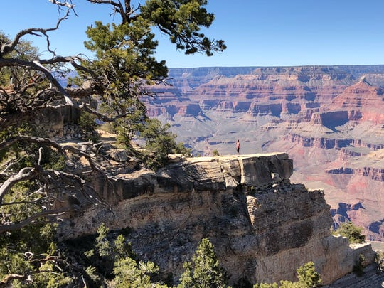 A visitor poses for a photo on a ledge off the Grand Canyon's South Rim.