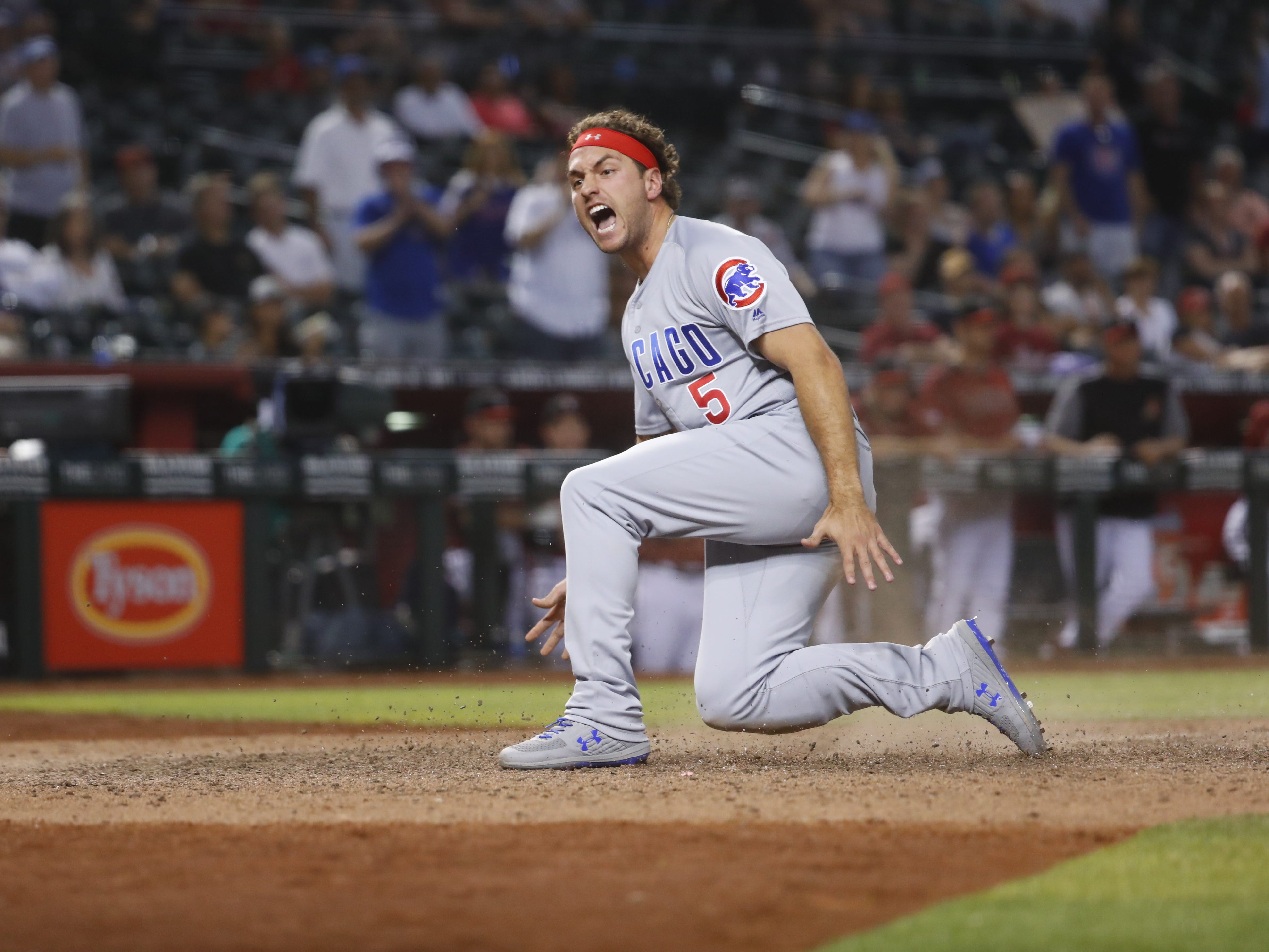 Cubs' Albert Almora Jr. (5) slides in scoring and celebrating against the Diamondbacks during the 15th inning at Chase Field in Phoenix, Ariz. on April 28, 2019.