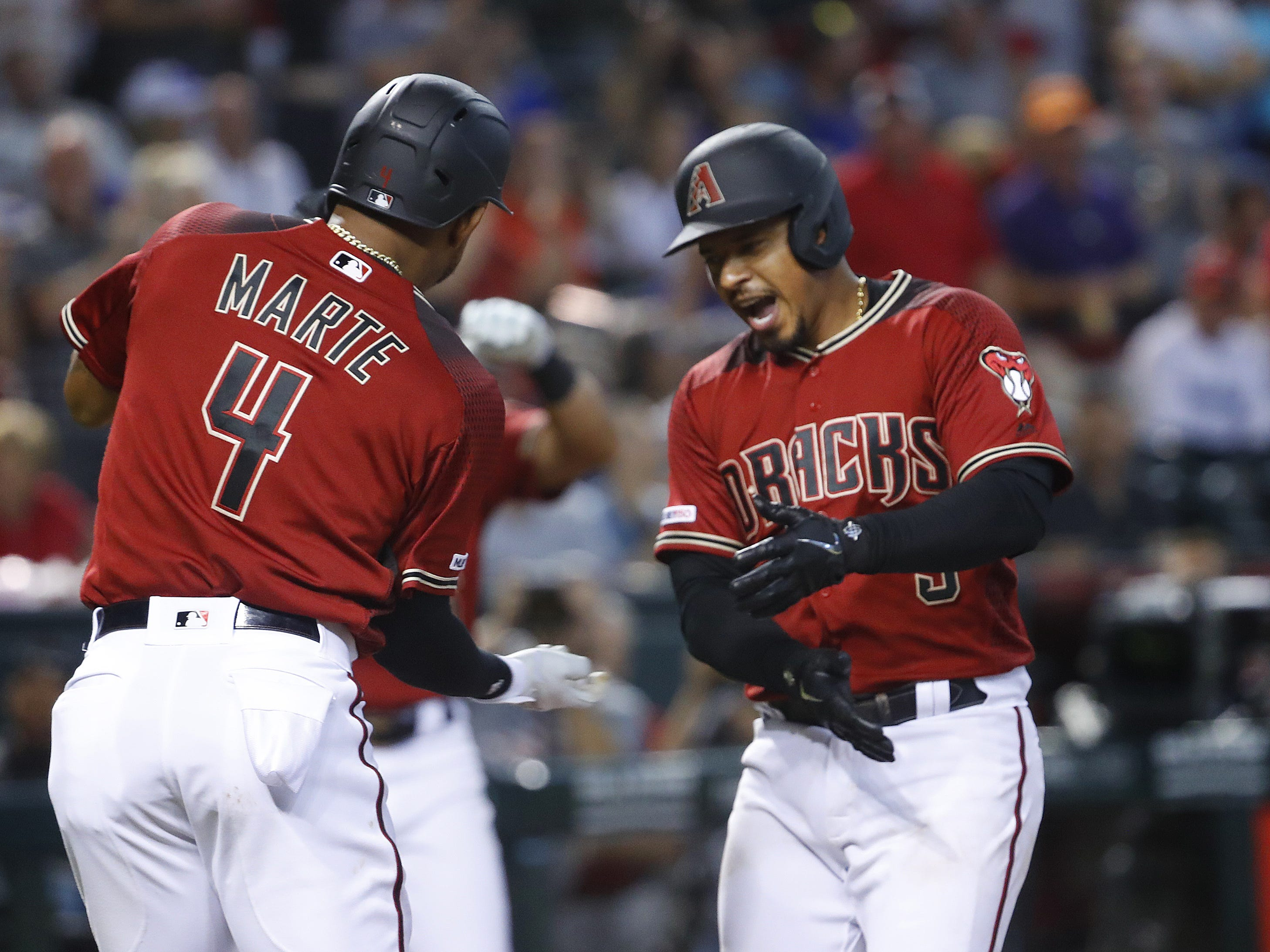 Diamondbacks Eduardo Escobar (5) celebrates at home with Ketel Marte (4) after hitting a two-run homer during the sixth inning against the Cubs at Chase Field in Phoenix, Ariz. on April 28, 2019.