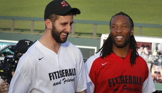 New Miami Dolphins' quarterback Josh Rosen shares a laugh with former teammate Larry Fitzgerald before the 9th Annual Larry Fitzgerald Celebrity Softball Game at Salt River Fields on Saturday, April 27, 2019, in Scottsdale, Arizona.