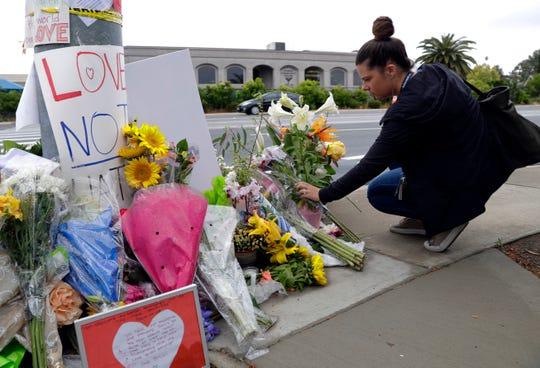 Una mujer deja flores en un altar improvisado en el lugar del tiroteo.
