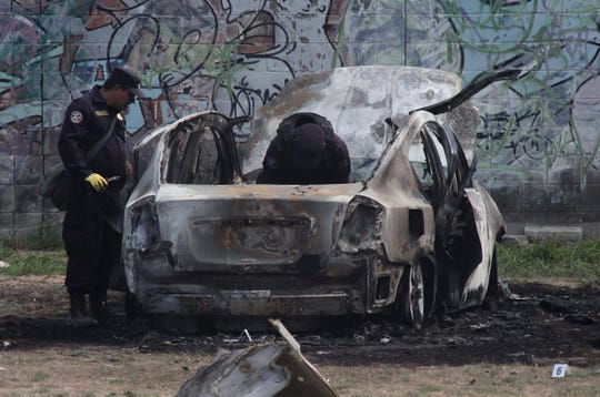 Policías revisan el auto que fue utilizado como coche bomba por las pandillas, en San Bartolo de Soyapango, El Salvador.