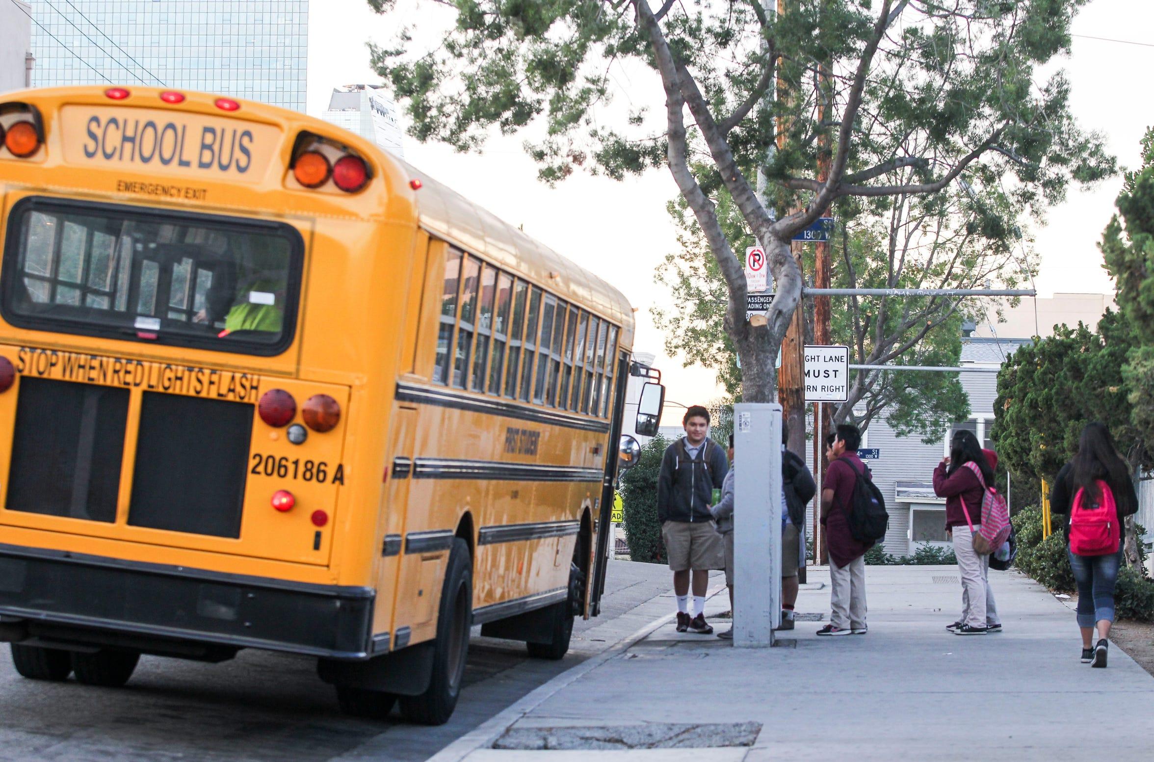 Estudiantes esperan en fila para abordar un autobús escolar. Foto archivo.