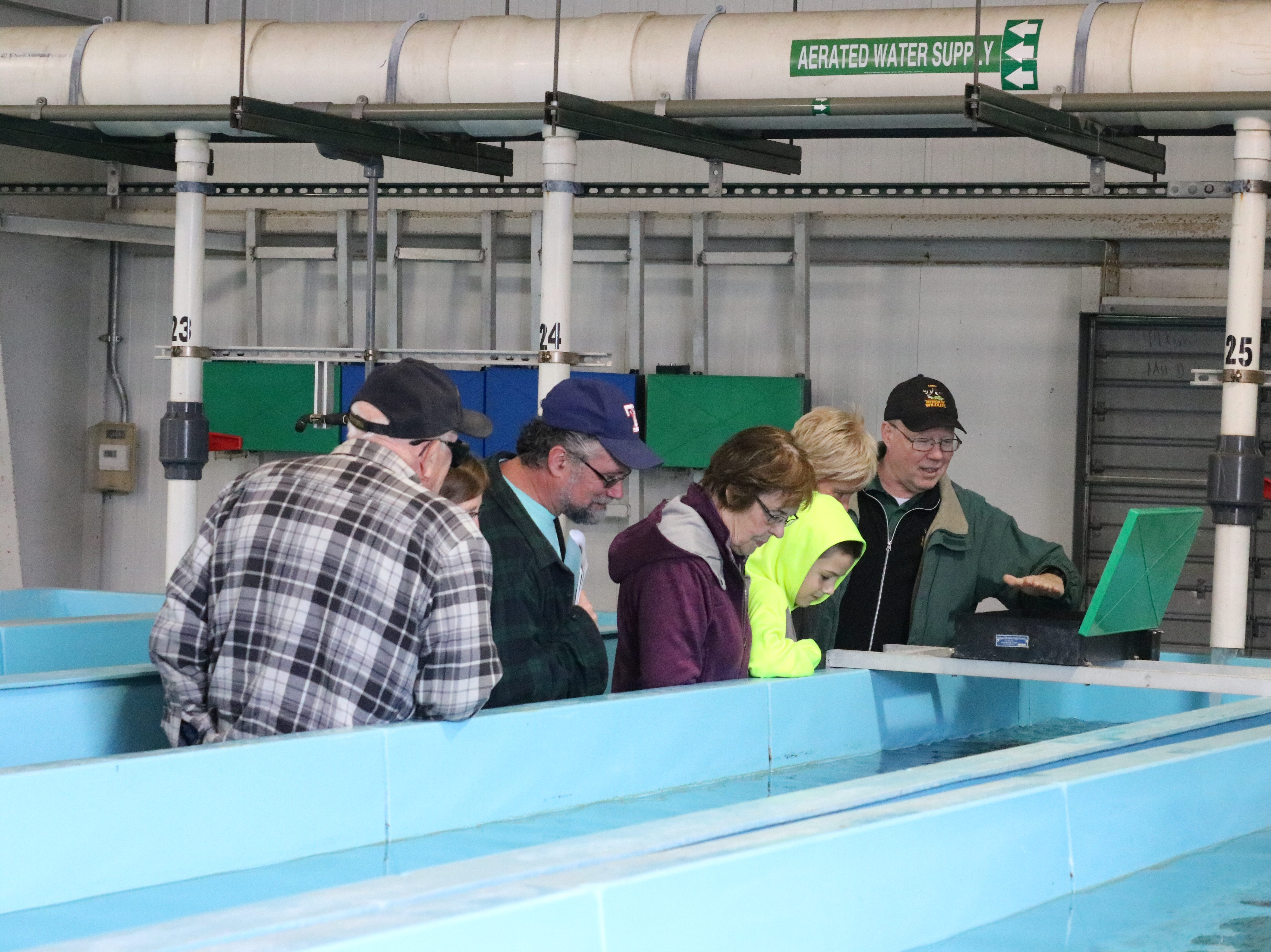 Kevin Kayle, administrator of the state fish hatchery program, speaks with the visitors during the open house in Castalia on Saturday.