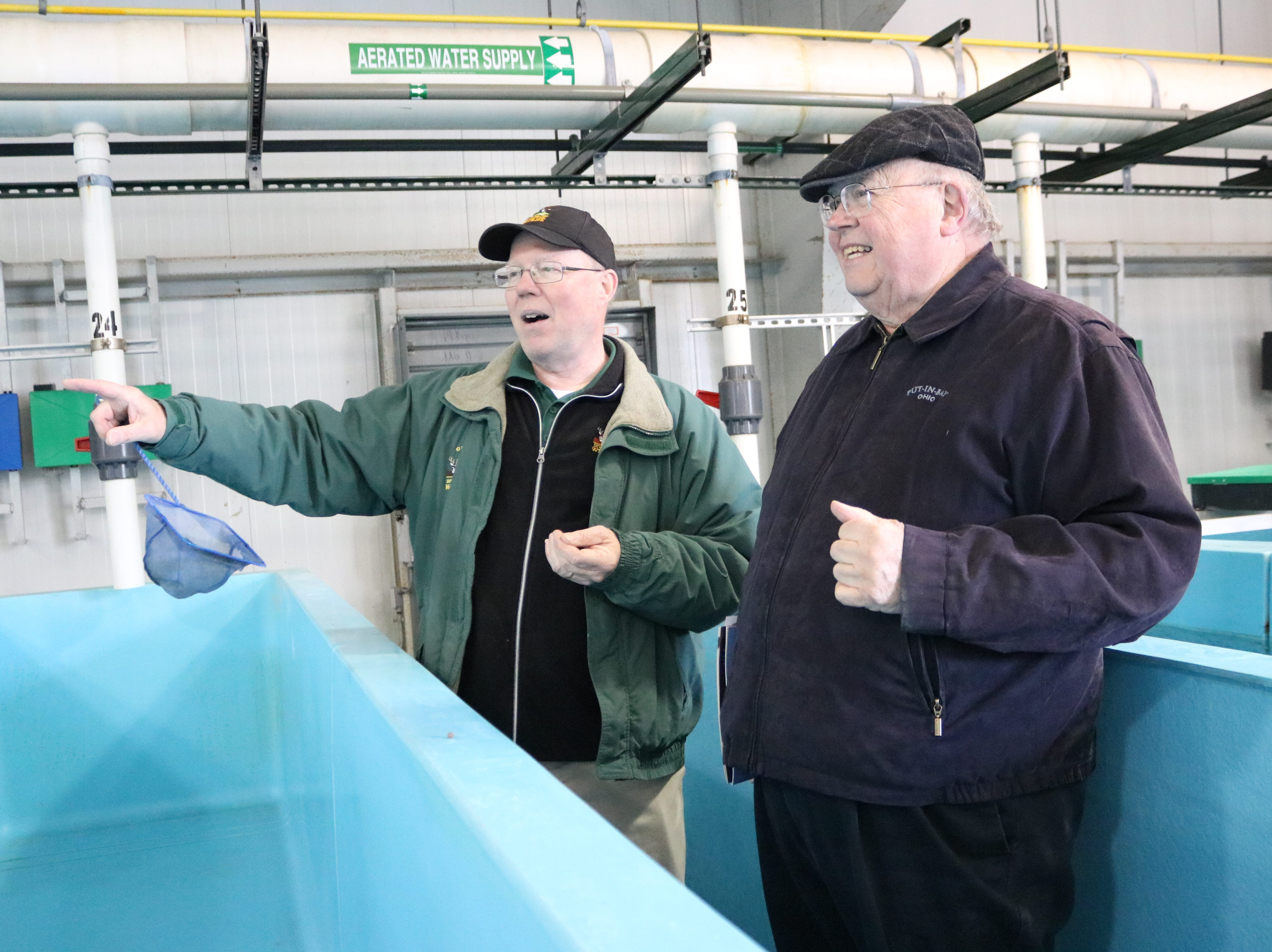 Kevin Kayle, administrator of the state fish hatchery program, speaks with the Rev. James Peiffer during the open house on Saturday.
