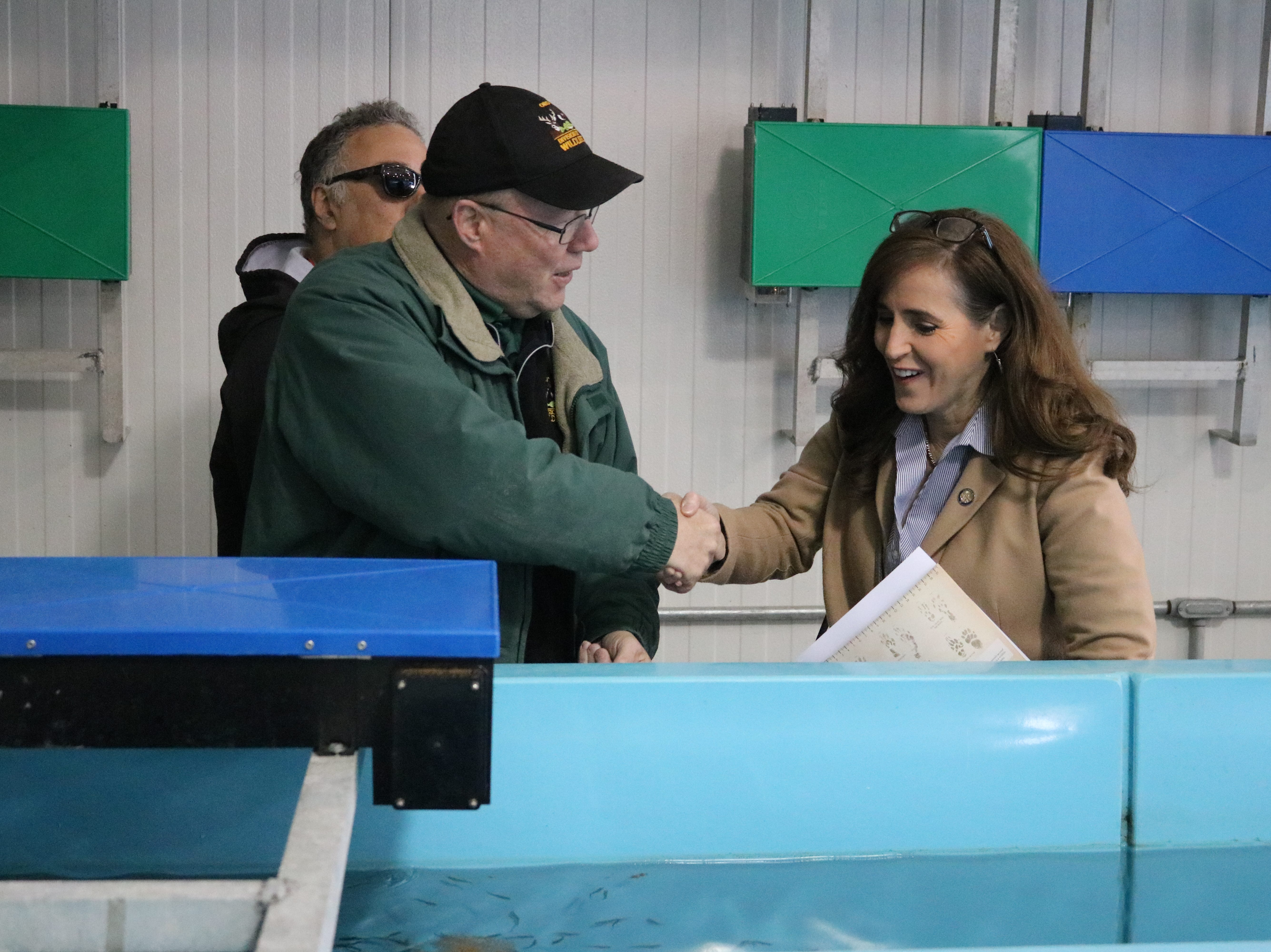Kevin Kayle, administrator of the state fish hatchery program, speaks with State Sen. Theresa Gavarone during the open house in Castalia on Saturday.