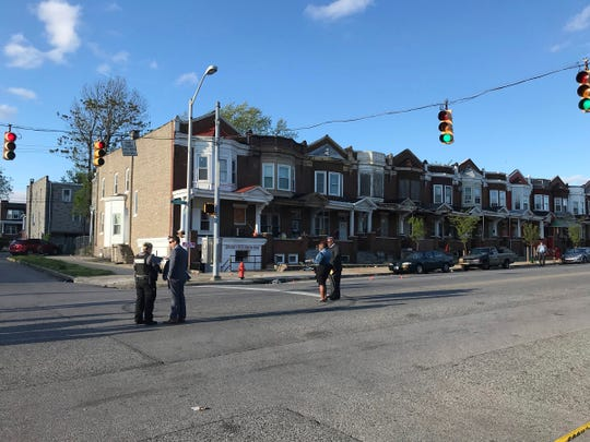 Authorities stand at Edmondson and Whitmore after multiple people were shot, Sunday, April 28, 2019, in Baltimore. (Kenneth K. Lam/The Baltimore Sun via AP)