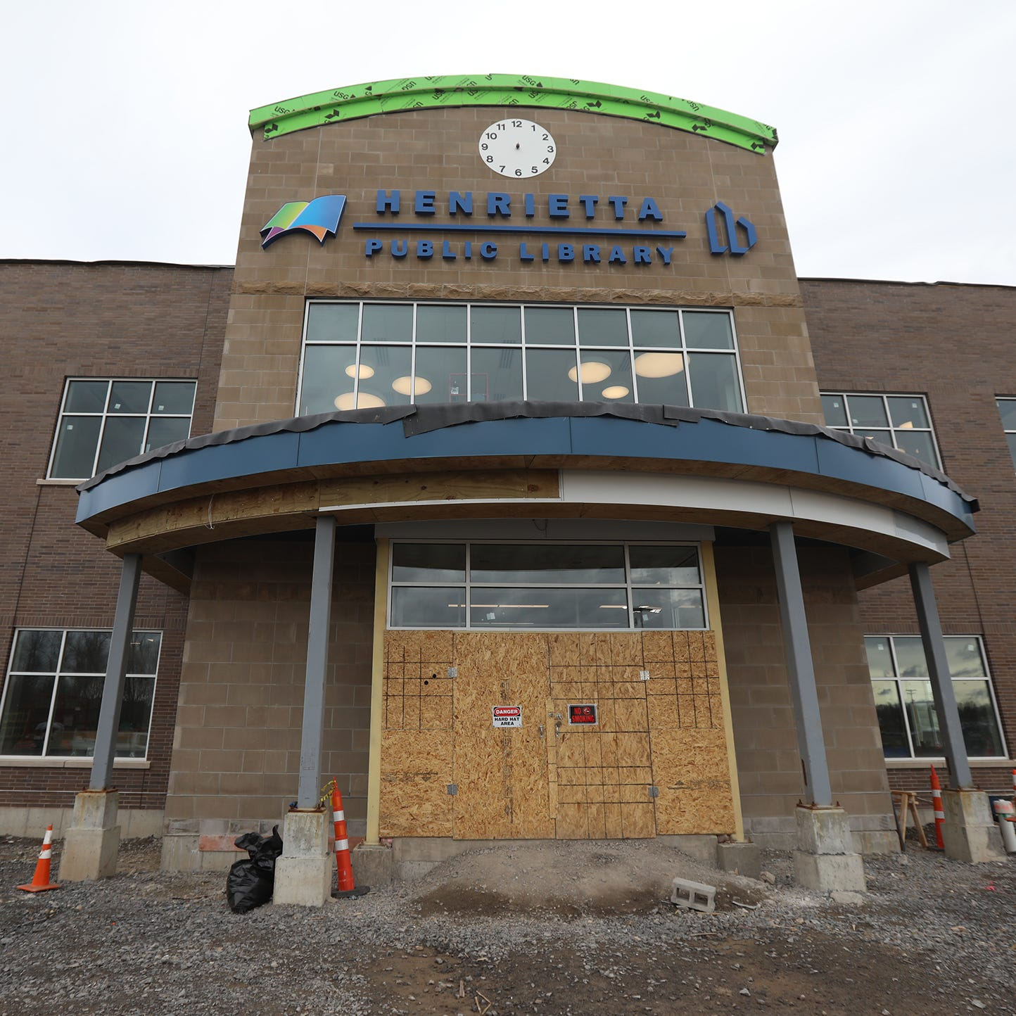 How did Henrietta's new library end up costing an extra $900,000?