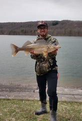 Adam Ballard with a walleye caught at Hemlock Lake