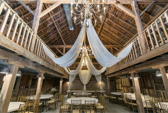The main reception area features seating on the main level along with the old hayloft. The original corn crib serves as a background for the bridal parties' table.
