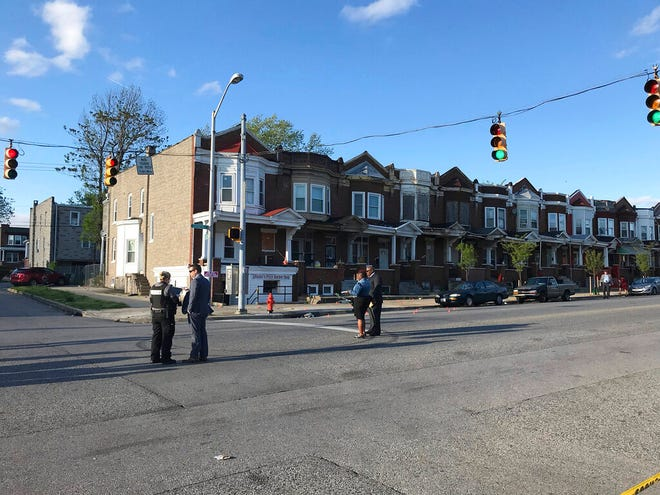 Authorities stand at Edmondson and Whitmore in after multiple people were shot, Sunday, April 28, in Baltimore.