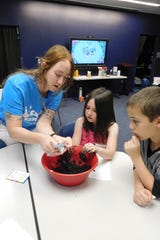 Layne Mikesell adds seeds to the soil mixture while campers look on eagerly.