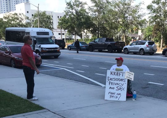 A man sits with a sign outside the Palm Beach County courthouse Monday morning, ahead of a hearing at which lawyers are expected to argue why videos of New England Patriots owner Robert Kraft allegedly receiving illegal sex services at a spa should be suppressed.