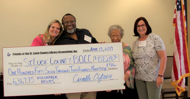 St. Lucie County Commission Vice Chair Cathy Townsend, left, with Friends of St. Lucie County Library Treasurer Padrick Pinkeny, President Carnelle Clifton and County Commission Chair Linda Bartz accepting the ceremonial check with the value volunteers brought to the library system in 2018.