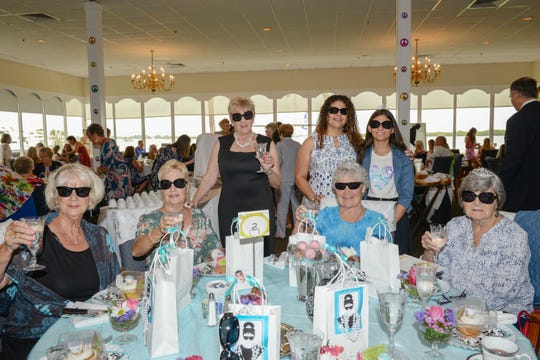 """Liz Hancock, standing, from left, and Carmen and Hailey Morales with, seated, Susan Arndt, Sandy Arnold, birthday girl Linda Chinn and MaryAnne Purdy at Treasure Coast Hospice's """"Time for Tea, A Journey through the Decades"""" fundraiser at Pelican Yacht Club."""