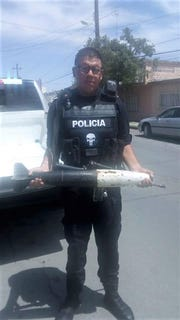 """A police officer holds a """"missile"""" surrendered during a gun buyback in Juárez, Mexico."""