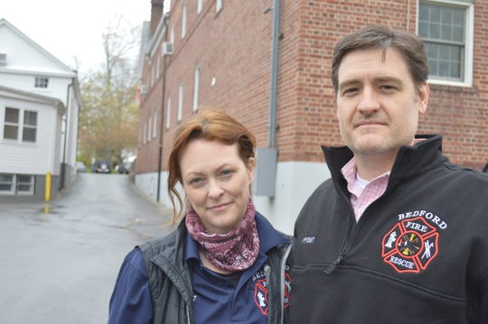 Bedford Fire District Chair Heather Feldman and Vice-chair Kyle Carleton stand behind the Bedford firehouse, which shares the alleyway with the US Postal Service.