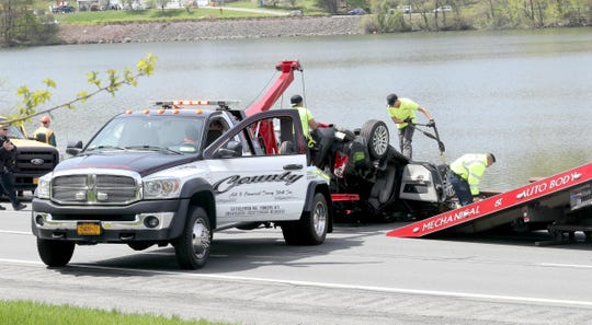 Tow truck operators pull a car onto a flatbed tow truck after pulling it out of the Grassy Sprain Reservoir along the Sprain Brook Parkway in Yonkers April 29, 2019. The car was traveling in the northbound lanes of the Sprain Parkway when it went into the water between Tuckahoe Road and Jackson Avenue at about 10:45 a.m. Two people were taken from the water with unknown injuries.
