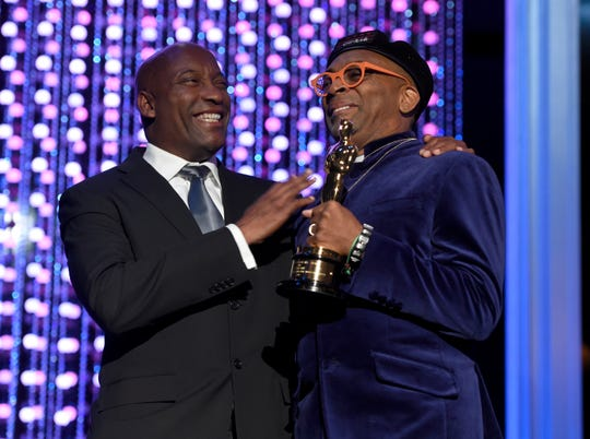 FILE - In this Nov. 14, 2015 file photo, John Singleton, left, and Spike Lee, honorary Oscar recipient, pose onstage at the Governors Awards in Los Angeles. Oscar-nominated filmmaker John Singleton has died at 51, according to statement from his family, Monday, April 29, 2019. He died Monday after suffering a stroke almost two weeks ago. (Photo by Chris Pizzello/Invision/AP, File)