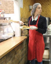 Actress and Wilmington native Aubrey Plaza picks up plates of baked ziti Monday at Wilmington's Emmanuel Dining Room before delivering them to people in need.