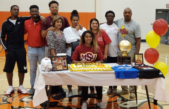 Burkburnett senior Eternity Jackson (sitting center) is joined by her family as they celebrate her signing to play basketball at Midwestern State University.