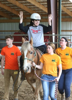 "Amanda Dilley, 21, has been riding at the Breaking Free Therapeutic Riding Center for nearly a decade. Amanda was diagnosed with epilepsy and autism and suffers from cerebral palsy in her legs. Her mother, Kathy, said the riding has helped Amanda in many ways. ""She's fearless and likes riding. I'm glad a program like this exists so she has something to help her out,"" she said."