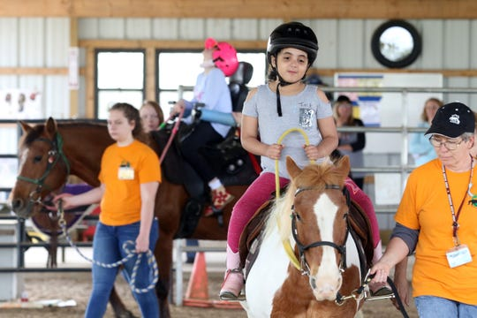 Alivia Harding and Abigail Cork, left, ride horses at Breaking Free Therapeutic Riding Center..