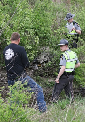 Highway Patrol Troopers and Scott Ford from Ford's Towing at the scene of a motorcycle wreck near Trinway Monday afternoon.