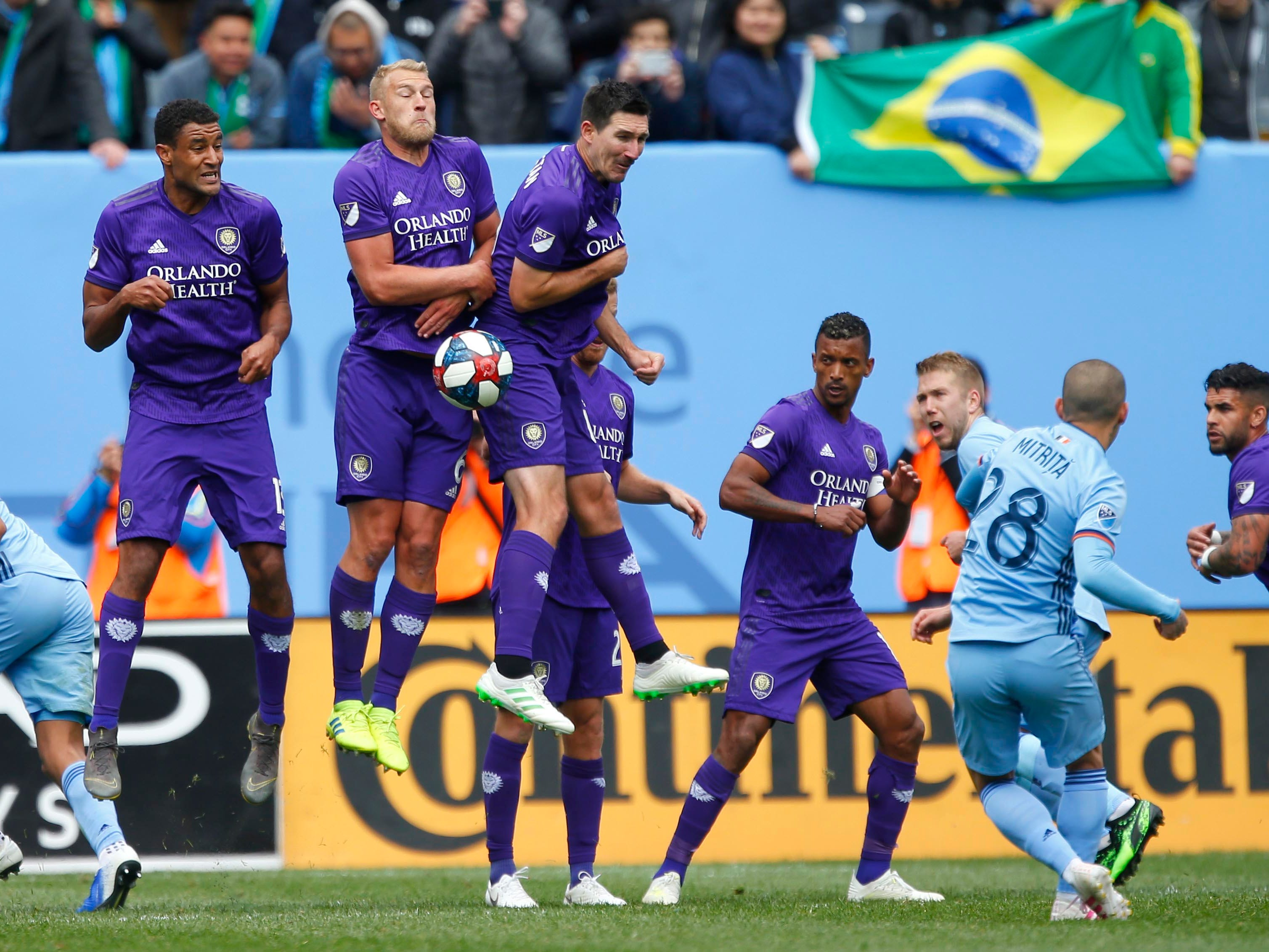April 27: Orlando City's Tesho Akindele (13), Robin Jansson (6) and Sacha Kljestan (16) defend a penalty kick by New York City FC's Alexandru Mitrita (28) during the second half at Yankee Stadium. The game ended in a 1-1 tie.