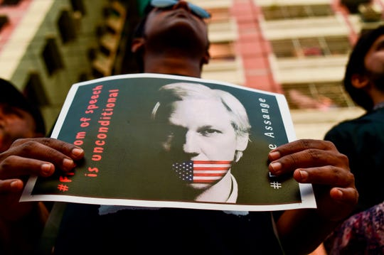 An activist holds a placard calling for the freedom of WikiLeaks founder Julian Assange, in Dhaka on April 23, 2019.