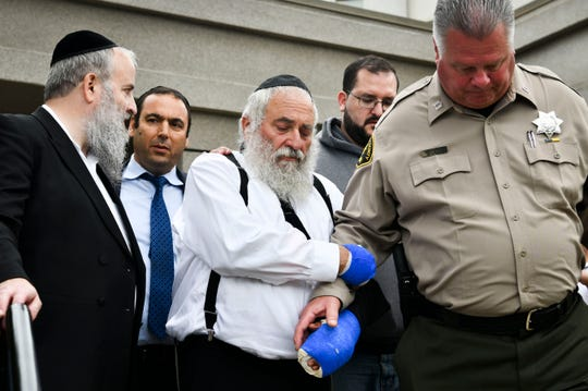 Rabbi Yisroel Goldstein, center, receives assistance from Capt. Jeff Duckworth of the Poway Sheriff's Station, right, following a Sunday afternoon news conference in front of the Chabad of Poway synagogue.