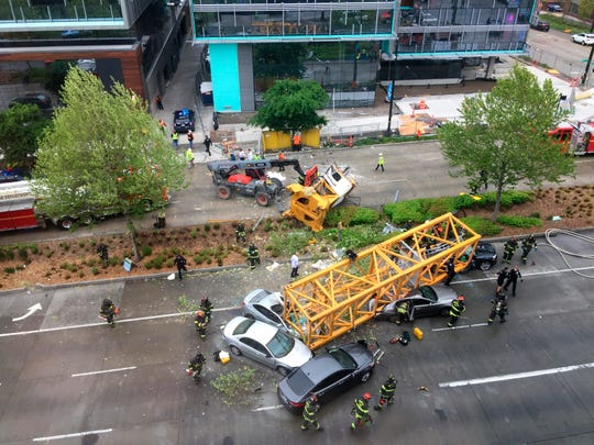 Fire and police crew members work to clear the scene where a construction crane fell from a building on Google's new Seattle campus crashing down onto one of the city's busiest streets and killing multiple people on Saturday, April 27.